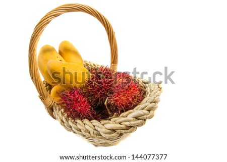 Rambutan and mango fruits in a basket over white background