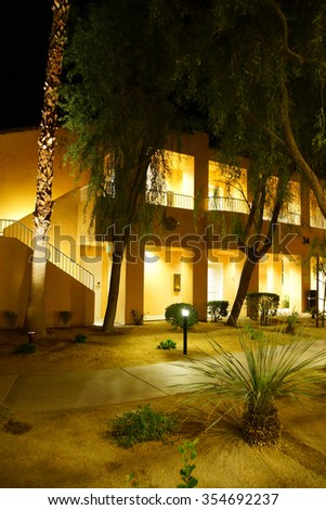 RANCHO MIRAGE, CALIFORNIA - DEC 16, 2015 - Night lights of Southwestern style hotel buildings in green oasis with Palm trees,  Rancho Mirage, California