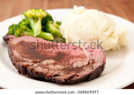 rare roast beef with vegetables, mashed potatoes and gravy