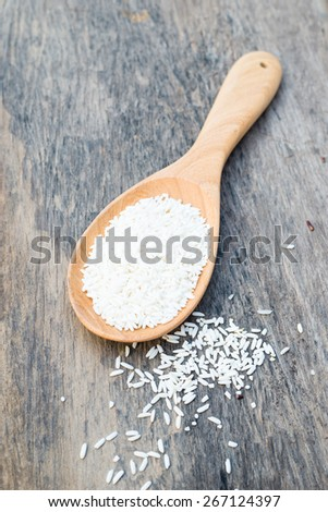 Raw and uncooked rice in wooden spoon over wooden background
