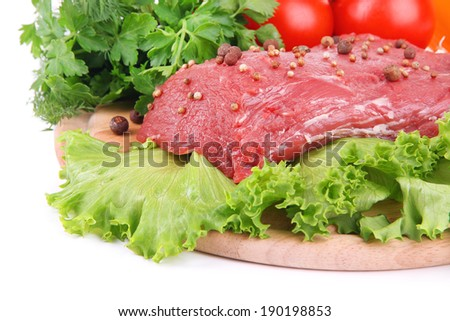 Raw beef meat with vegetables on wooden cutting board close up
