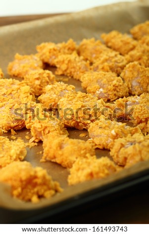 Raw breaded in corn flakes chicken fillet on baking sheet. Making oven baked corn flake crumbs chicken nuggets. Series.