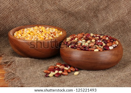 Raw corn, and beans in wooden bowls on table on sackcloth  background