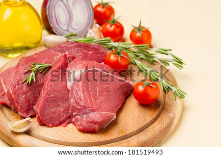 Raw meat on round board, tomatoes, onions, oil and rosemary