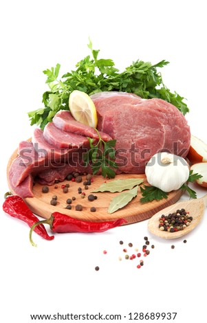 Raw meat, vegetables and spices on a wooden cutting board isolated on white background.