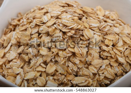 Raw oatmeal heap in the bowl over wooden background