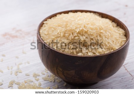 Raw rice in wooden  bowl on white wooden background. Selective focus.