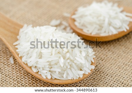 Raw rice in wooden spoon on sack background.