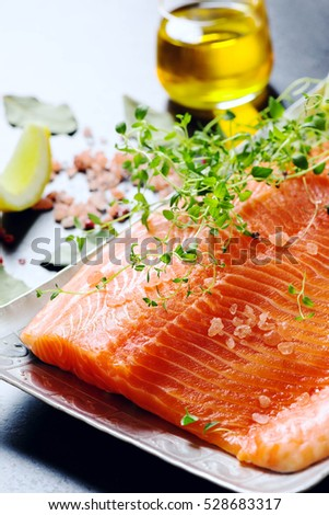 raw salmon fillets on aluminium trey with lemon and spices