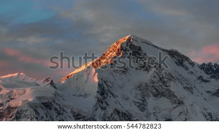 Rays of sunset on the tops of the mountains on a sunny day - Gokyo region, Nepal, Himalayas