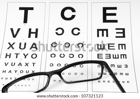 Reading eyeglasses and eye chart. close-up. on a light gray background
