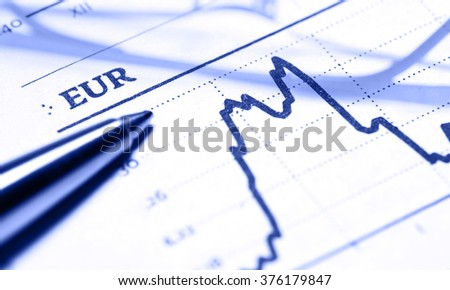 Reading glasses and pen over financial market graph. Business concept.