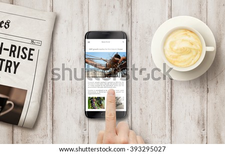 Reading news article on the phone during coffee time. Newspapers, coffee on the wooden table with top view.