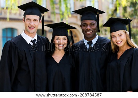 Ready to bright future. Four college graduates in graduation gowns standing close to each other and smiling