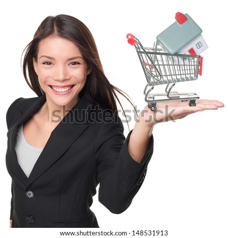 Real estate agent selling home holding mini house in shopping cart. Female realtor in business suit showing model house smiling happy isolated on white background. Multiracial Asian woman agent.