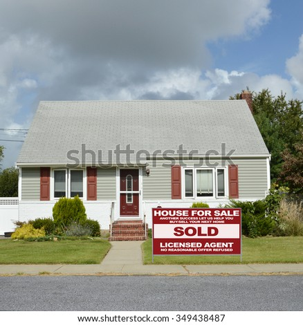 Real estate sold (another success let us help you buy sell your next home) sign Suburban Cape Cod Style home residential neighborhood USA Cloudy blue Sky day