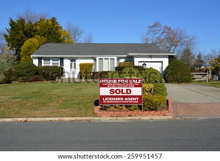 Real estate sold (another success let us help you buy sell your next home) sign Suburban Ranch style home clear blue sky residential neighborhood USA