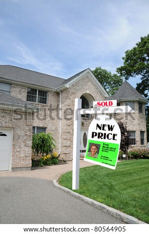 Realtor Real Estate Sold For Sale Sign Post in front of Luxury Suburban Home