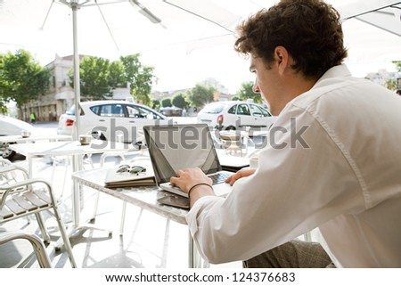 Rear side view of a young businessman using a laptop computer while sitting at a coffee shop terrace table under a parasol, outdoors.