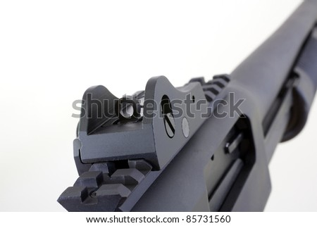 Rear sights that are peeps on a pump action shotgun on white