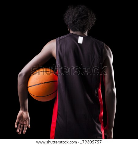 Rear view of a basketball player holding a ball against dark background