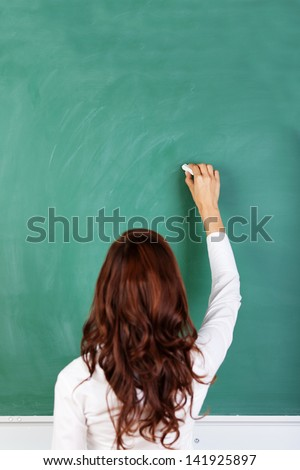 Rear view of a student or teacher with long brunette hair writing on a blank green blackboard or chalkboard with copyspace
