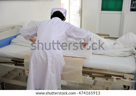 Rear view of  asian nurse caring for patient.