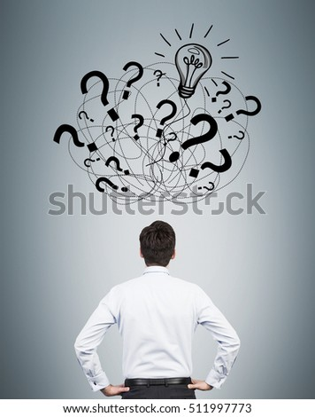 Rear view of businessman looking at multiple question mark sketches and a bulb on gray wall. Concept of finding the answer