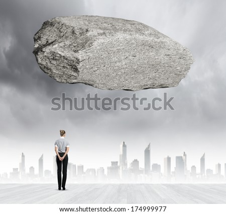 Rear view of businesswoman looking at urban scene with huge stone above