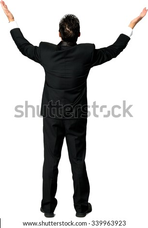 Rear view of Caucasian man with short black hair in a tuxedo with arms open - Isolated