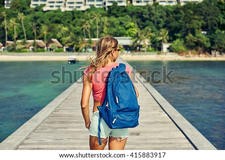 Rear view of hipster girl carrying backpack on her back