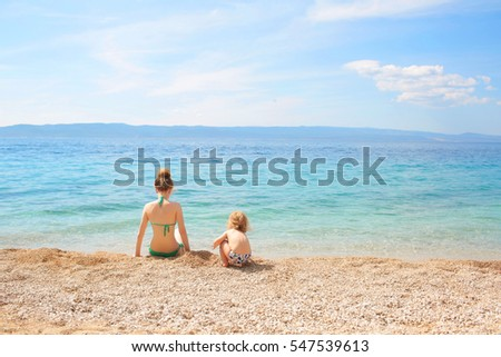 Rear view of mother and child in swimsuits sitting on beach of pebbles and looking at sea, copy space
