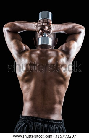 Rear view of muscular man lifting dumbbell against black background
