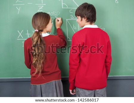 Rear view of teenage students looking at each other while writing on board in classroom