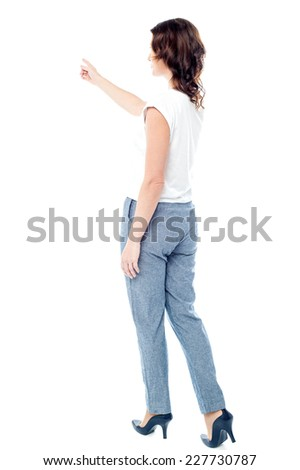 Rear view of woman pointing her finger at something