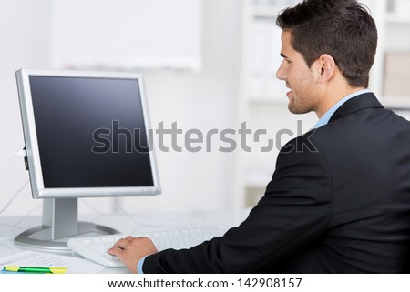 Rear view of young businessman using computer at desk in office