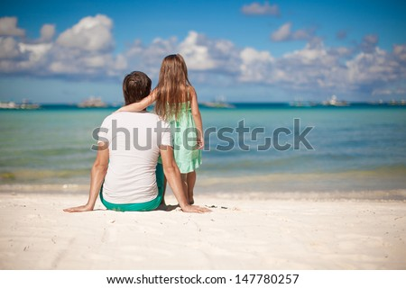 Rear view of young father and his little daughter look at the sea