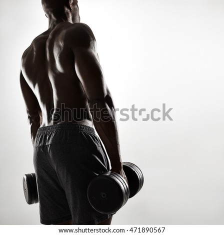 Rear view shot of muscular young african man exercising with dumbbells. Fit black male model with heavy dumbbells over grey background.