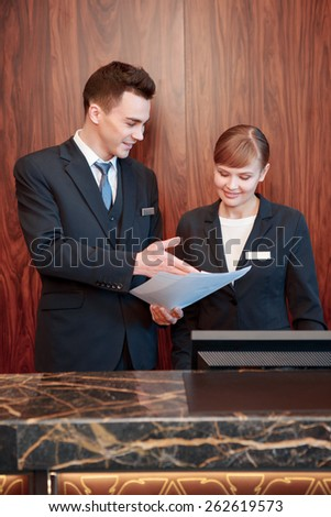 Reception at work. Male receptionist shows business papers to the female receptionist to discuss operating activity
