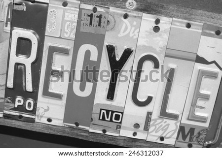 Recycle sign made out of state license plates.  Each letter, spelling the word recycle, is a piece of a state license plate