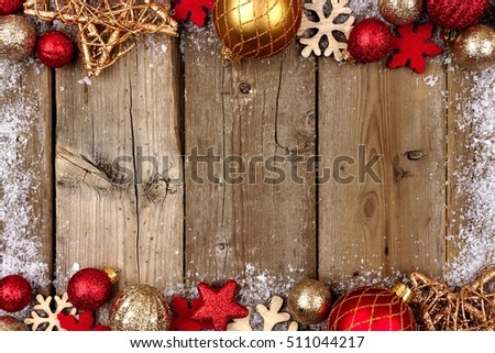 Red and gold Christmas ornament double border with snow frame on a rustic wood background