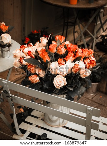 Red and pink roses bouquet with empty price tag in metal bucket standing on the chair. Aged photo.