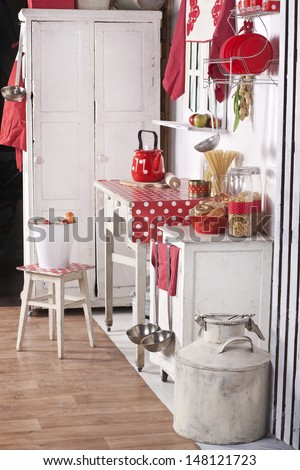 red and white kitchen with old furniture, food and utensils in a country house