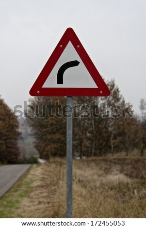 Red and white road sign showing curve ahead. Closeup. Copy space
