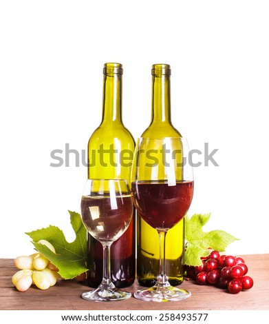 Red and white wine in bottles and glass on the wooden table