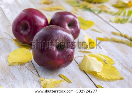 Red apples and yellow leaves on wooden background, selective focus
