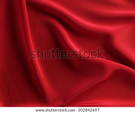 red background photo of wavy folds of silk satin or velvet material or luxurious red background with elegant curves of red material for Christmas