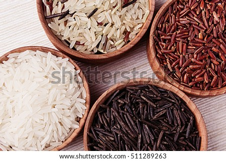 Red, black and white rice close-up in wood bowls on beige fabric. Rice texture background.