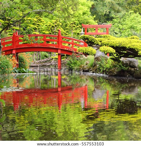 Red bridge over water in Japanese garden