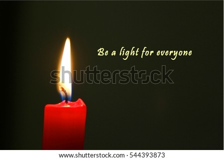 Red candle illuminating dark background with english text